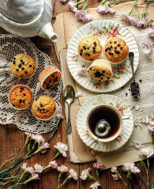 dei muffin visti dall'alto con gocce di cioccolato, una tazza fi the e una teiera