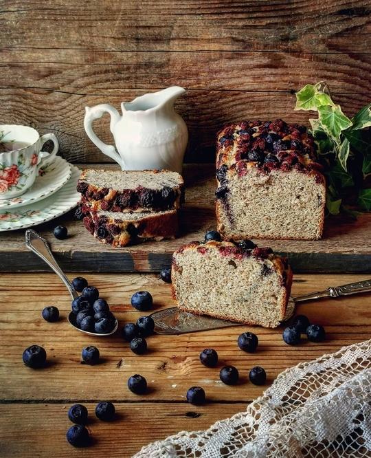 un plumcake tagliato con una brocca di latte a lato e una tazza vintage con del the, tanti mirtilli sparsi sul tavolo