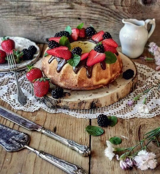 una ciambella coperta da ganache al cioccolato e frutta, su un tavolo di legno, a lato una bricchetto bianco