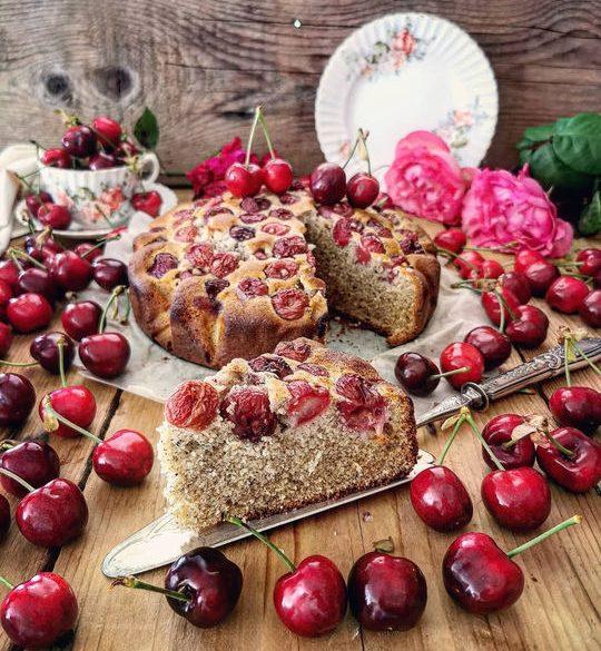 una torta con le ciliegie, posata sul un avolo di legno con tutte ciliegie intorno e una fetta tagliata in primo piano