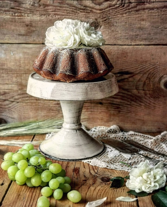 una alzata con una torta decorata con fiori bianchi, sotto posato sul tavolo di legno un grappolo di uva bianca