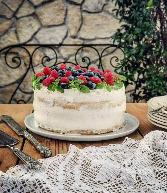 una torta alta con la panna e frutta, posata su un tavolo di legno