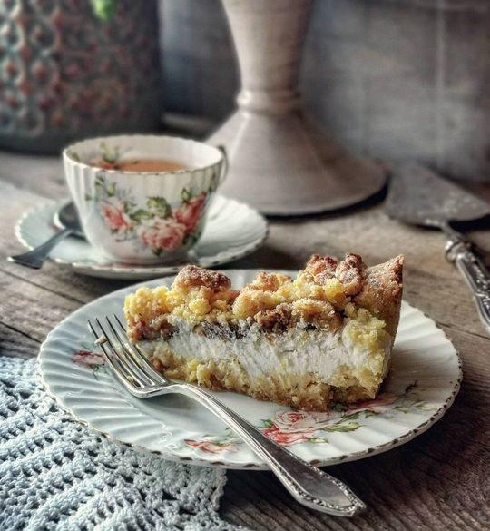 un piattino vintage con una fetta di crostata ripiena di ricotta in primo piano, sullo sfondo una tazza di the