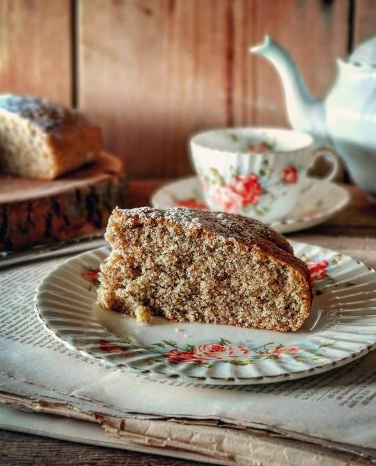 un piattino con una fetta di torta, dietro una teiera e una tazza di the vintage