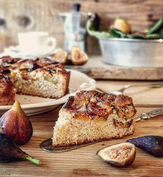 una fetta in primo piano di torta di fichi, a lato fichi e una torta tagliata, sullo sfondo una moka e una tazza
