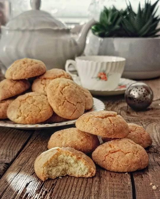 tanti biscotti e in primo piano uno con un morso, sullo sfondo teiera bianca e tazza di the