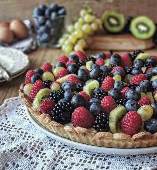 una crostata di frutta in primo piano, sopra un centro in pizzo bianco, sullo sfondo uva, uova e kiwi