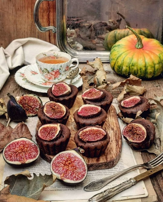 muffin cacao e fichi sul tavolo di legno, sullo sfondo una tazza di the e una zucca