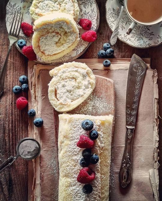 un rotolo di crema con frutti rossi vista dall'alto con frutti di bosco, a lato un coltello e due fette tagliate