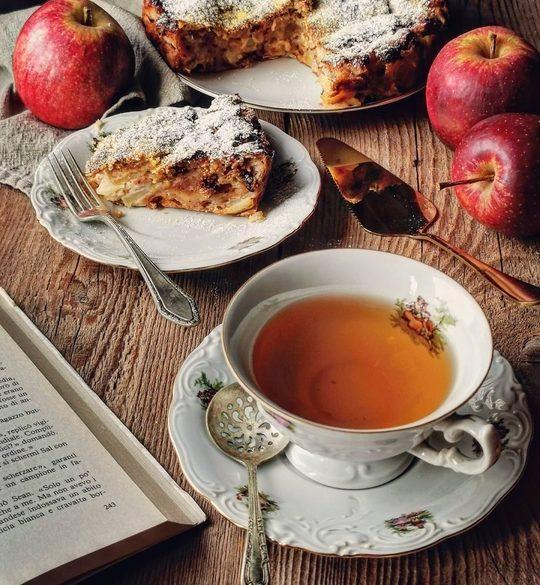 una tazza di the in primo piano, un libro aperto, un piattino con una fetta di torta con delle mele rosse