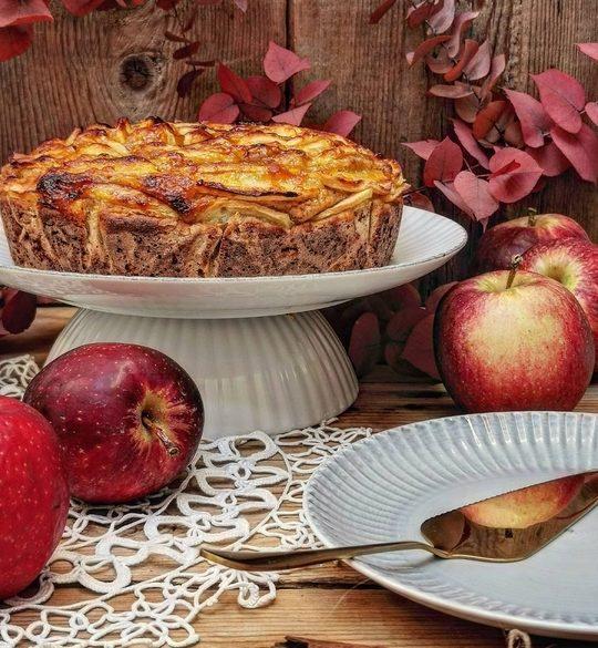 tavolo di legno e una torta di mele su una alzata bianca, a lato delle mele rosse, un piatto con una paletta oro