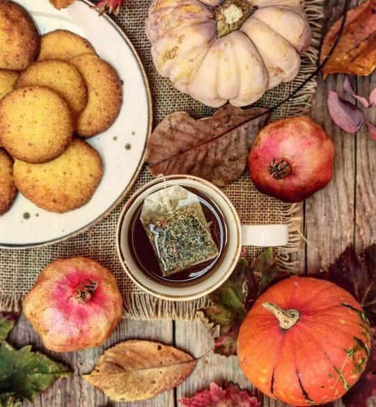 un tavolo visto dall'alto, una tazza di the, zucche, foglie, piattino con biscotti dorati