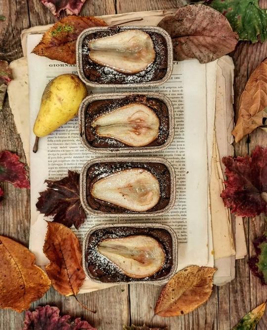 uno scatto dall'alto con quattro miniplumcake al cacao con le pere tagliate a metà, a lato fogli e pera gialla