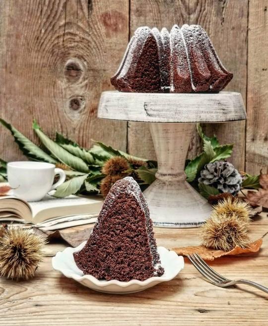 una fetta di torta al cacao in primo piano con tanti ricci di castagna sul tavolo, sullo sfondo una alzata con la torta spolverata di zucchero a velo.