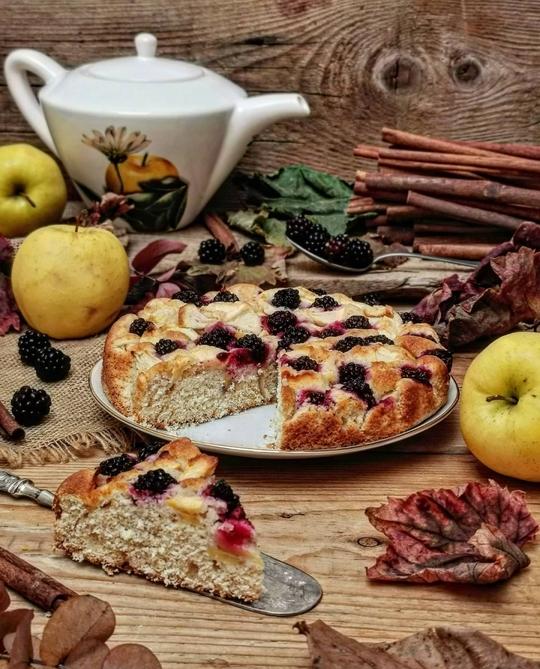 un tavolo di legno con una torta di mele e more tagliata, una fetta in primo piano , sullo sfondo una teiera, fogli e mele gialle a lato