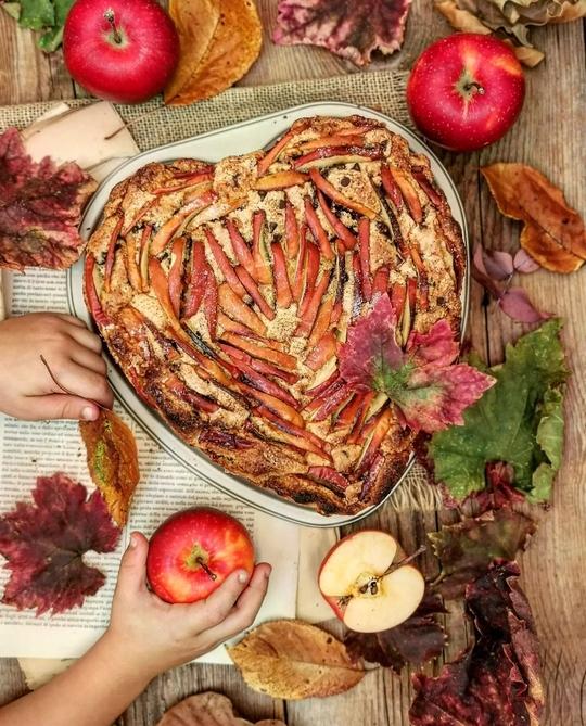 una torta a cuore di mele vista dall'alto, una manina che afferra una mela